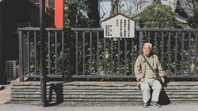 老人坐长凳 浅草,日本 免版税库存照片