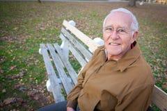 老人坐长凳 免版税库存照片