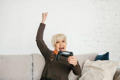 老人妇女播放她赢的一个电子游戏和姿态 年长人和现代技术 库存图片