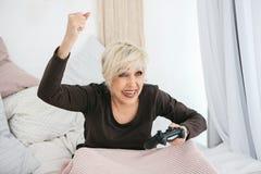 老人妇女播放她赢的一个电子游戏和姿态 年长人和现代技术 图库摄影