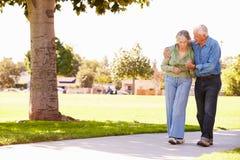老人帮助的妻子,他们在公园一起走 免版税图库摄影