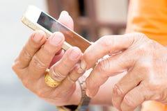 老人戏剧的手与老智能手机电话的 库存图片