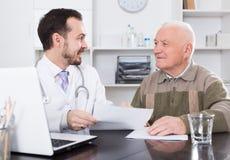 老人拜访医生 免版税库存照片