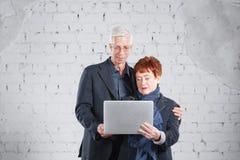 老人拿着一台膝上型计算机并且通过互联网沟通 站立愉快的微笑的祖父祖母的夫妇拥抱 免版税库存照片