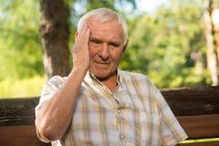 老人拿着他的头 免版税库存图片
