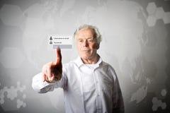 老人按真正按钮 注册和密码concep 图库摄影