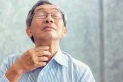 老人接触他的脖子和有痛苦在喉头 免版税图库摄影