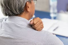 老人支持脖子和肩膀痛苦使用手按摩和摩擦 免版税库存图片