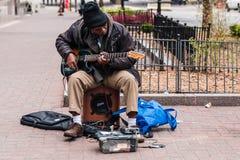 老人无家可归的使用的吉他乞求为了金钱能生存 免版税图库摄影