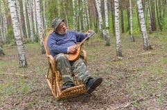 老人有休息在桦树森林 图库摄影
