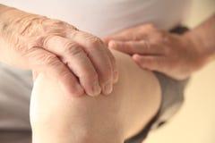 老人有在一个疼痛膝盖的手 免版税库存图片
