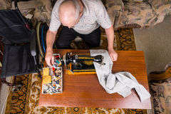 老人有缝纫机的修补工作裤子 免版税库存照片