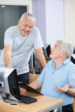 老人有讨论在计算机类 免版税图库摄影
