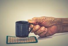 老人有黑杯子的手举行在白色桌上 免版税图库摄影