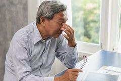 老人注重疲乏,并且握他的鼻子遭受静脉窦痛苦疲劳 免版税库存照片