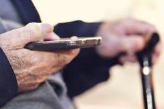 老人用一拐棍使用一个智能手机 免版税库存照片