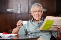 老人用咖啡和报纸 库存照片