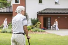 老人用在逗留期间的拐棍在护理房子里 Bl 库存图片