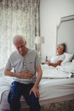 老人用手坐坐在卧室的胃 库存照片
