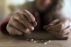 老人用计数硬币的肮脏的手 库存图片