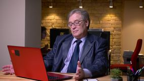 老人画象玻璃的在正式服装与是的膝上型计算机一起使用殷勤的在办公室 影视素材