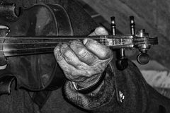 老人的手和小提琴 免版税库存图片