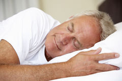 老人睡着在床上 免版税图库摄影