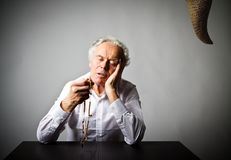老人祈祷与念珠小珠 祷告和诱惑 免版税库存图片