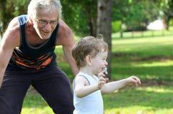 老人祖父追逐的孙子在公园 免版税库存图片