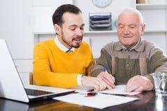 老人签的汽车购买契约 免版税库存照片
