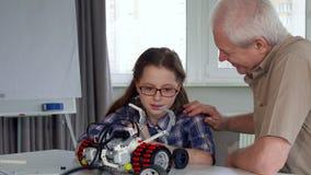 老人给他的孙女从玩具车的部分 免版税图库摄影