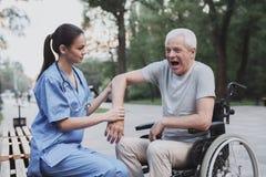 老人给护士审查伤害的他的手肘 库存图片