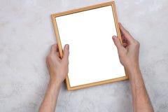 老人设法垂悬与一张照片的一个木制框架在Th 图库摄影