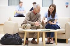 老人谈论结果与数字式片剂的护士 免版税库存照片