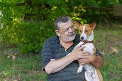 老人谈话与他采取它在手上的逗人喜爱的狗basenji,当休息在夏天公园时 免版税库存图片