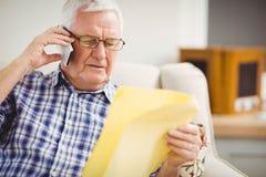 老人谈话在手机,当看文件时 库存图片