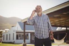 老人谈话在手机他的房子外 免版税库存图片