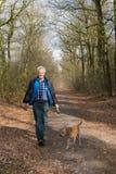 老人走的狗在森林里 免版税图库摄影