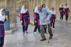 老人走通过在城市街道,设拉子,伊朗上的女小学生 免版税库存照片