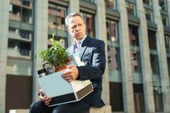 老人起了皱纹拿着他的个人箱子的办公室经理 免版税库存照片
