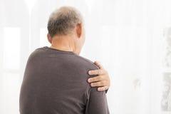 老人遭受的肩膀痛苦 免版税库存照片