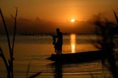 老人钓鱼在日落 免版税库存照片
