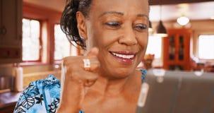 老人非裔美国人的妇女在她的厨房使用她的片剂 免版税库存照片