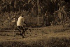 老人骑马自行车在农村地方 图库摄影