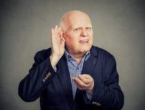 老人,有点聋,安置手在耳朵要求某人毫无保留地说出  免版税库存照片