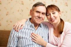 老人,有他们的照料者的妇女在家 免版税图库摄影
