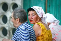 老人:一条长凳的三个俄国领抚恤金者在公寓的入口附近 库存照片