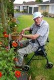 老人: 坐的从事园艺 免版税库存图片