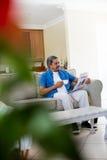 老人读书报纸,当食用咖啡时 免版税库存照片