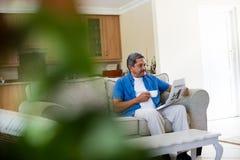 老人读书报纸,当食用咖啡时 库存图片